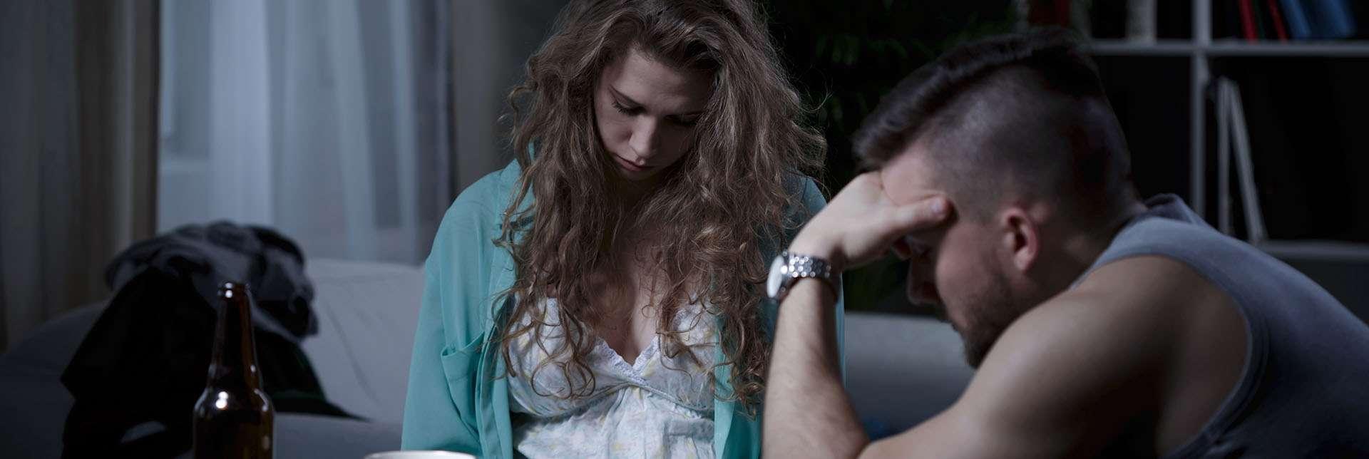 Mann og kvinne sitter i sofa med bøyde hoder og trist blikk. Temabilde: vold i nære relasjoner