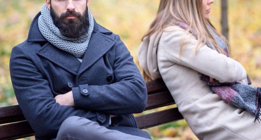 Bilde av par som sitter på benk og ser hver sin vei
