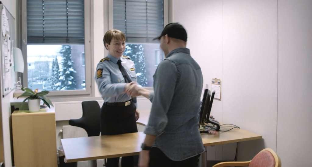 mann hilser på kvinnelig politioverbetjent