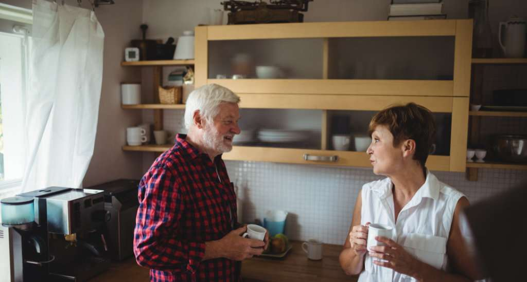 Eldre par som står sammen på et kjøkken