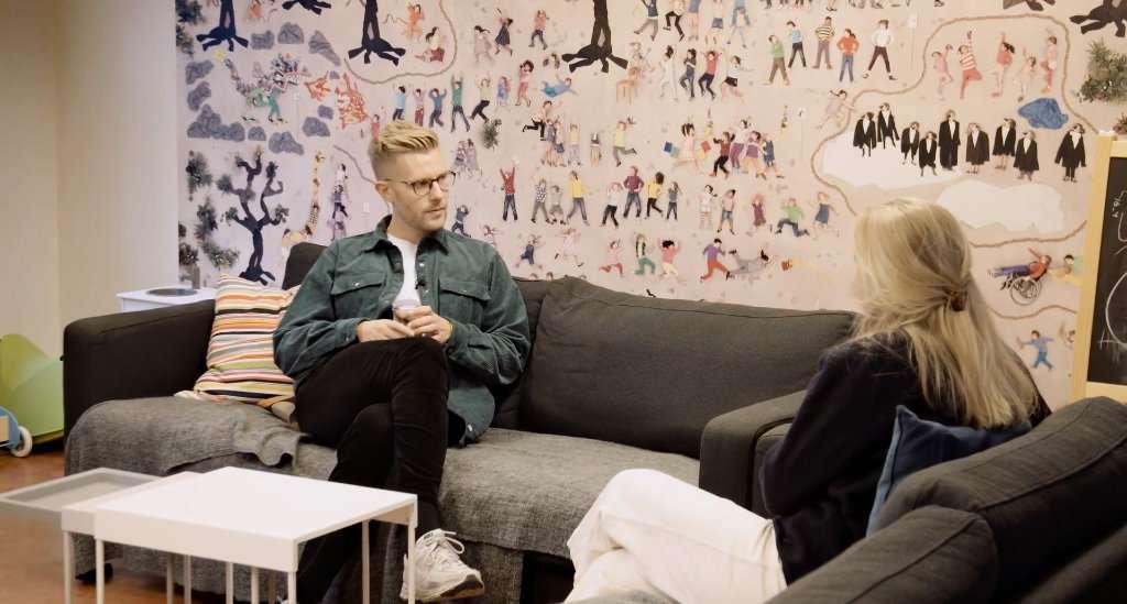 En mann og en kvinne sitter på hver sin sofa og snakker sammen
