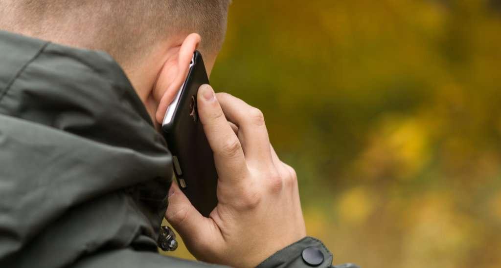 baksiden av mann som snakker i telefon