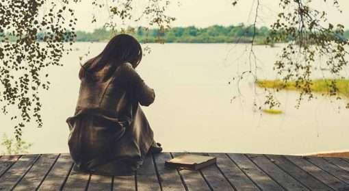 Jente sitter på brygge og ser utover vannet. Det kan være tungt å være usikker på om det man har opplevd var voldtekt.